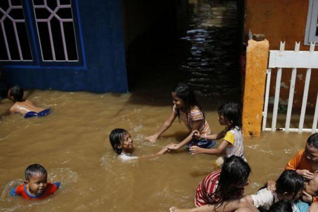 BANJIR DI JAKARTA: Kanak-kanak di daerah Kampung Melayu di Jakarta kelihatan bermain air apabila air mula naik ekoran hujan lebat. - Foto REUTERS