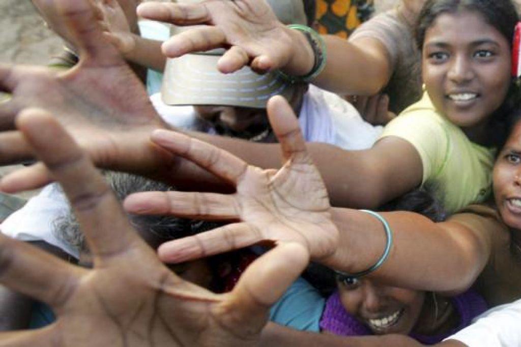 TINGGAL KENANGAN: Foto bertarikh 29 Disember 2004 ini menunjukkan mangsa tsunami berebut-rebut mendapatkan pakaian dan makanan yang didermakan oleh badan-badan di Cuddalore, selatan Madras, India. - Foto REUTERS