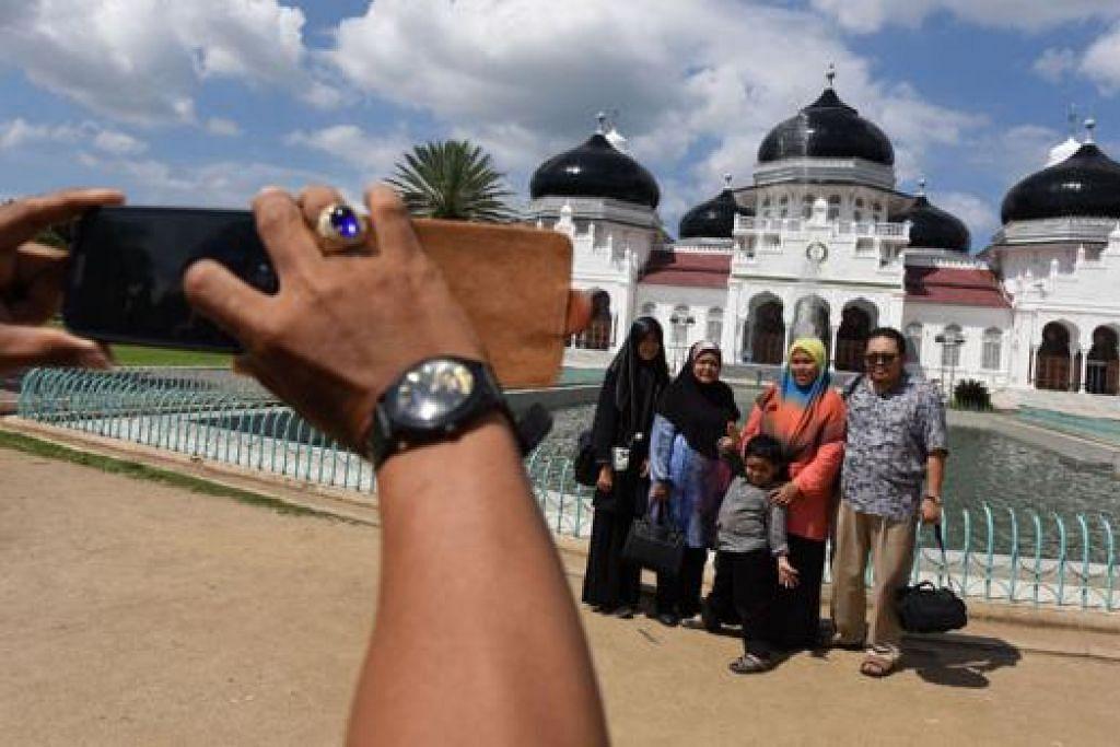 PULIH SELEPAS 10 TAHUN: Sebuah keluarga mengambil gambar kenang-kenangan di hadapan Masjid Besar di Banda Aceh, Indonesia pada 10 Disember lalu. - Foto BLOOMBERG