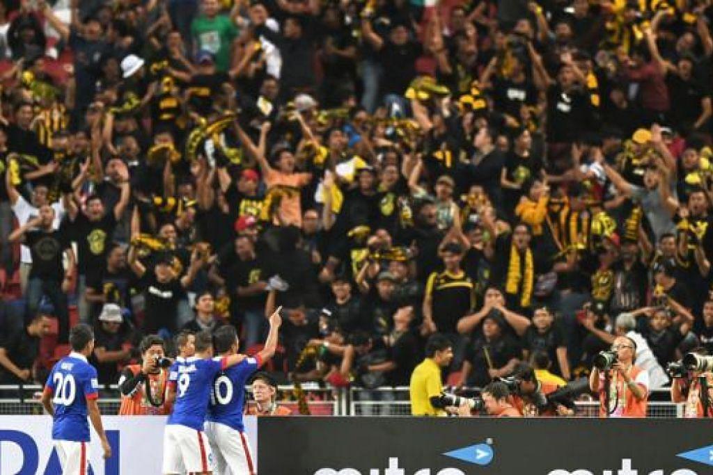MENANG SORAK: Penyokong Malaysia kegembiraan apabila pasukan negara itu menjaringkan gol pertama ke atas Singapura. - Foto AFP