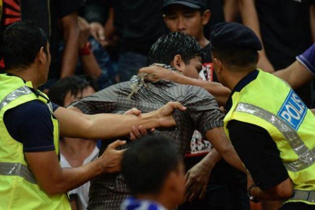 DIBERKAS POLIS: Seorang penyokong Malaysia ini diberkas semasa kekecohan yang berlaku dalam pertarungan separuh akhir pertama Piala AFF Suzuki menentang Vietnam baru-baru ini. - Foto-foto AFP