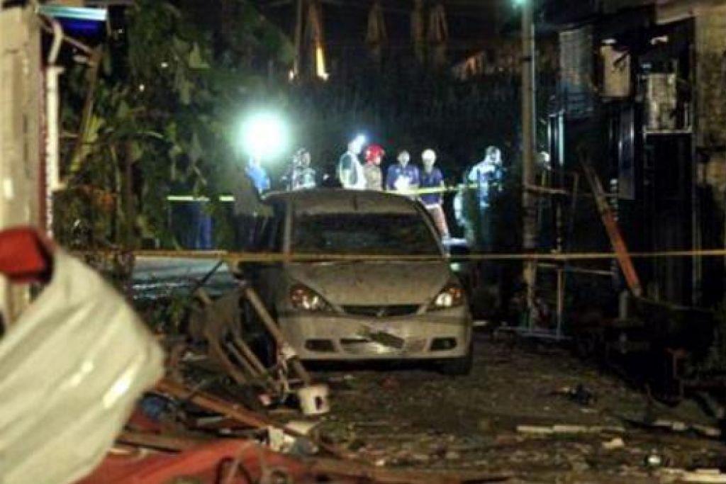KESAN LETUPAN: Pihak polis menjalankan siasatan terhadap beberapa rumah yang rosak teruk dan kereta akibat letupan di Gurun, Kedah. - Foto THE STAR