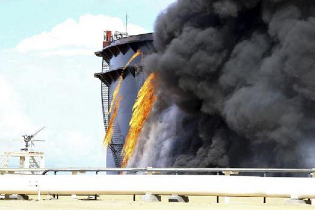 ROSAK DAN TERBAKAR: Asap hitam keluar daripada tangki mintak yang terbakar dekat Pelabuhan Al-Sidra setelah dibedil roket militan IS yang cuba menawan kawasan loji minyak itu. - REUTERS