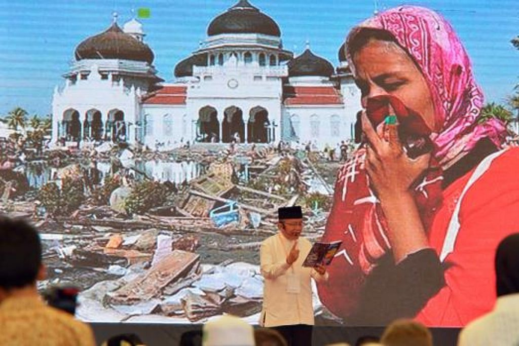 MENGENANG KEMBALI: Warga Aceh mengimbas semula kenangan pahit dilanda tsunami dengan wajah kesedihan jelas terpapar di wajah mereka. - Foto THE STRAITS TIMES