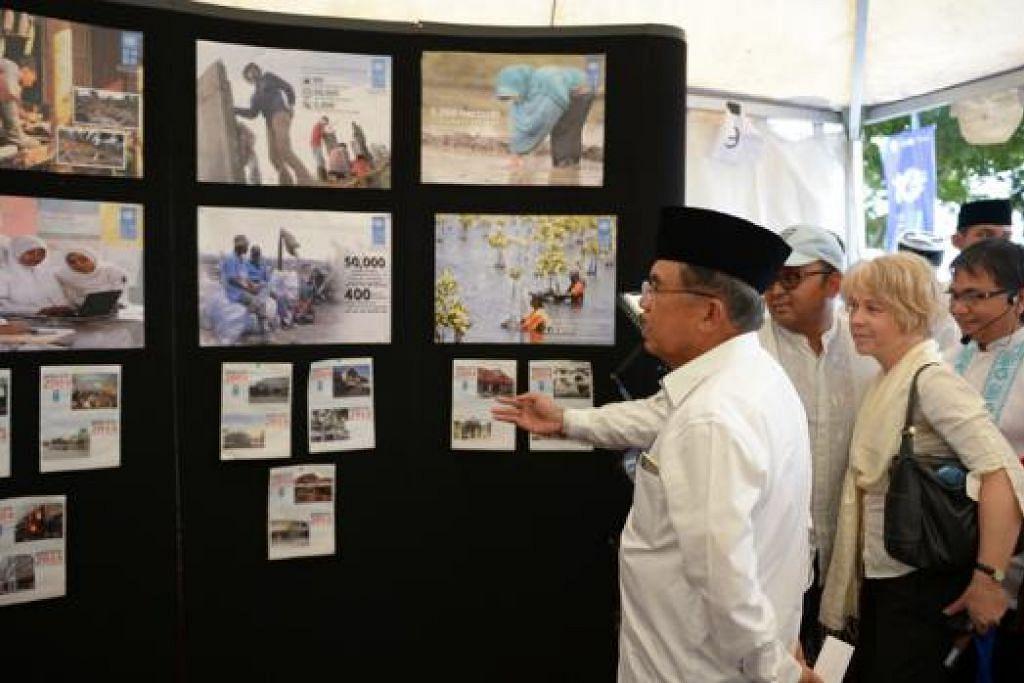KENANGAN PAHIT: Naib Presiden, Encik Jusuf Kalla, meninjau pameran bergambar menyentuh tentang tsunami yang melanda Aceh 10 tahun lalu.