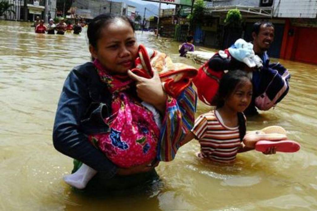 CARI TEMPAT SELAMAT: Para penduduk Dayeuhkolot di Bandung, Indonesia, mencari tempat yang lebih selamat. - Foto REUTERS