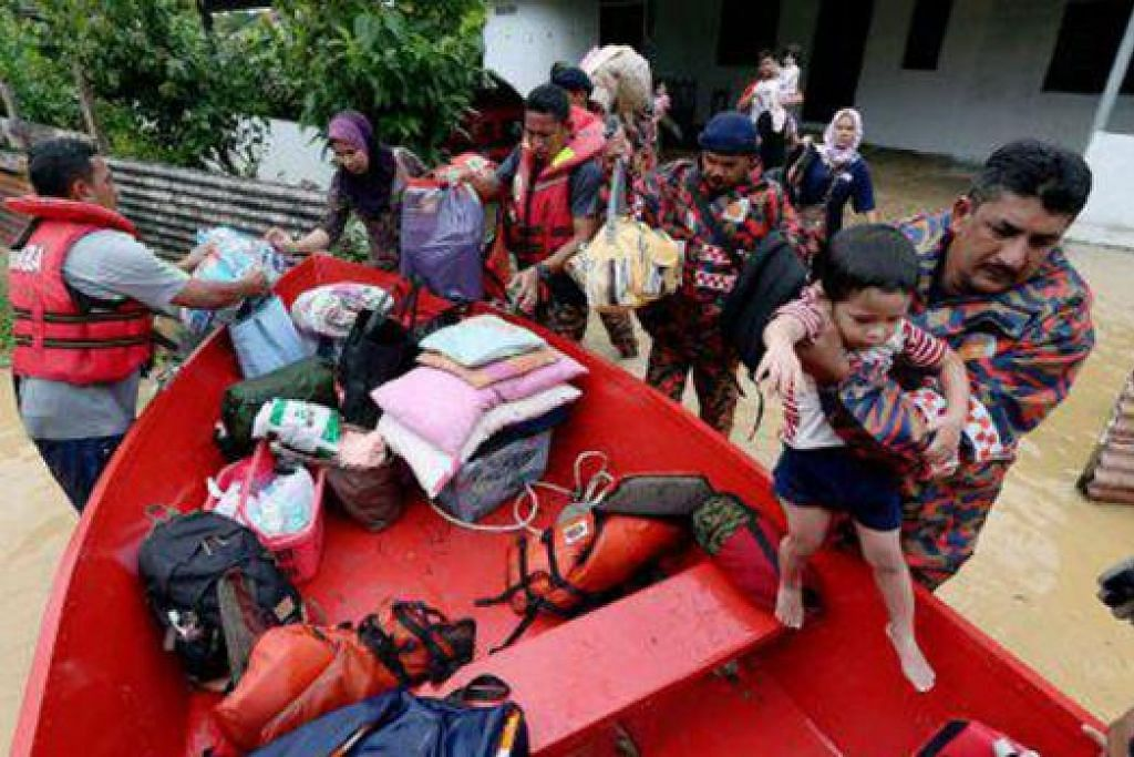 BANTUAN DIPERTINGKAT: Pasukan penyelamat membantu penduduk kampung di Kelantan berpindah dan dalam masa yang sama menghulurkan bantuan makanan kepada mereka. - Foto NST