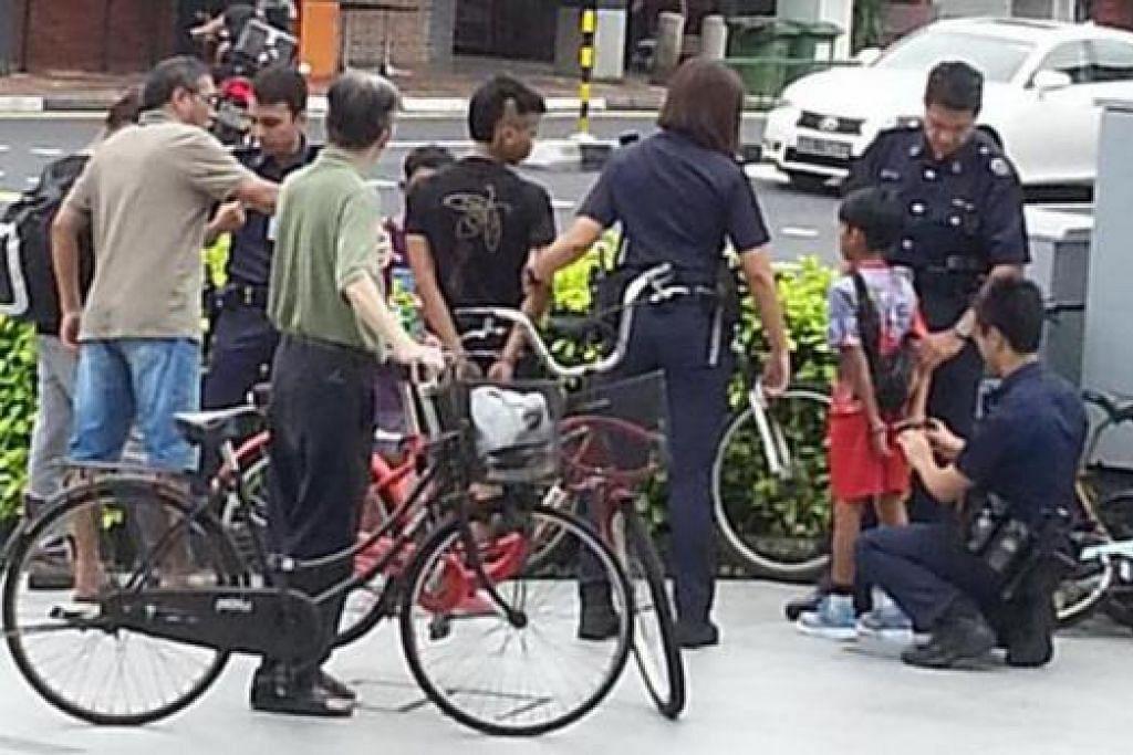 DISYAKI MENCURI: Polis dilihat menggari kanak-kanak yang disyaki mencuri di sebuah pusat beli-belah di East Coast Road semalam selepas mereka cuba melarikan diri. - Foto SHAN ANG