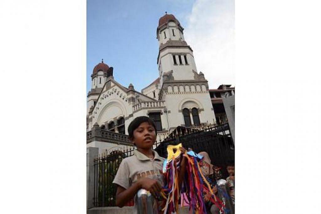 LAWANG SEWU: Seorang anak kecil, menjaja topeng untuk pelancong di gerbang masuk bangunan bersejarah Lawang Sewu. Bangunan itu pusat perusahaan kereta api awam pertama yang menghubungkan Semarang dengan Surakarta (Solo) dan Yogyakarta (Semarang-Tanggung) pada 1867. – Foto-foto MOHD SAMAD AFANDIE