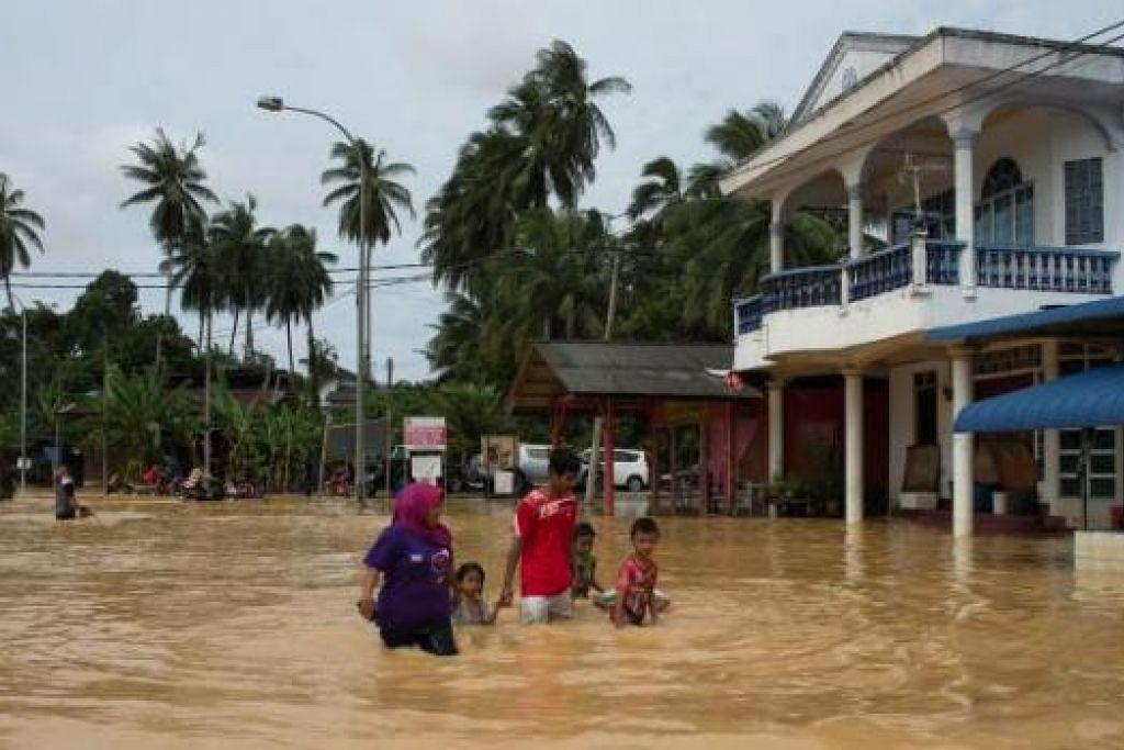 BELUM SURUT: Sepasang suami isteri bersama tiga anak mereka meredah banjir di Kota Bharu, Kelantan, ketika negeri itu mencatat bilangan mangsa tertinggi iaitu 42,469 orang daripada 9,663 keluarga di 62 pusat pemindahan. - Foto AFP