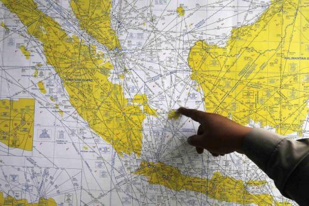Seorang anggota polis Indonesia sedang menunjukkan peta di sebuah pusat krisis di Lapangan Terbang Antarabangsa Juanda, Surabaya.