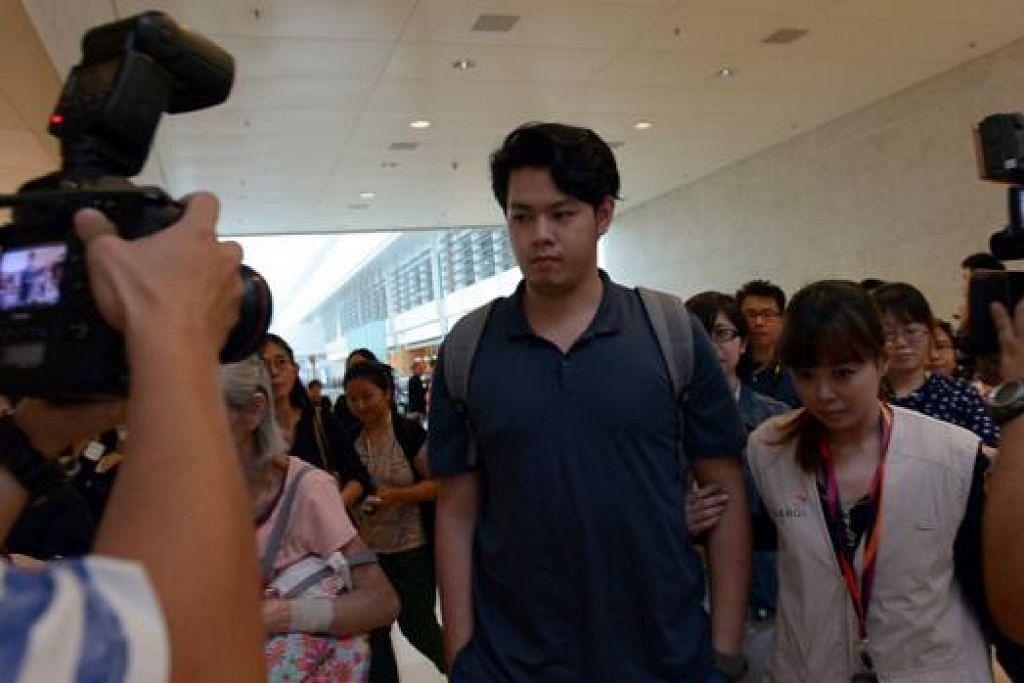 MENANTIKAN BERITA: Seorang anggota keluarga salah seorang penumpang diiringi pegawai masuk ke ruang khas yang disediakan bagi anggota keluarga di Terminal 2, Lapangan Terbang Changi semalam. - Foto-foto TUKIMAN WARJI