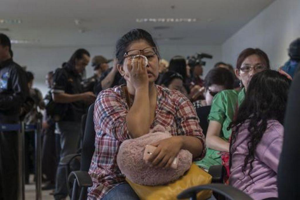 MENAHAN SEBAK: Anggota keluarga penumpang berkumpul di Lapangan Terbang Antarabangsa Juanda di Surabaya bagi menantikan berita tentang nasib penerbangan QZ8501. - Foto-foto AFP