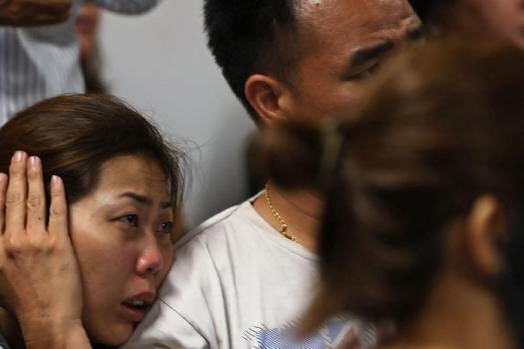MENUNGGU BERITA: Anggota keluarga penumpang AirAsia QZ8501 tidak dapat menahan sebak di saat menanti perkhabaran ketika berada di ruang menunggu di Lapangan Terbang Antarabangsa Juanda, Surabaya. - Foto REUTERS