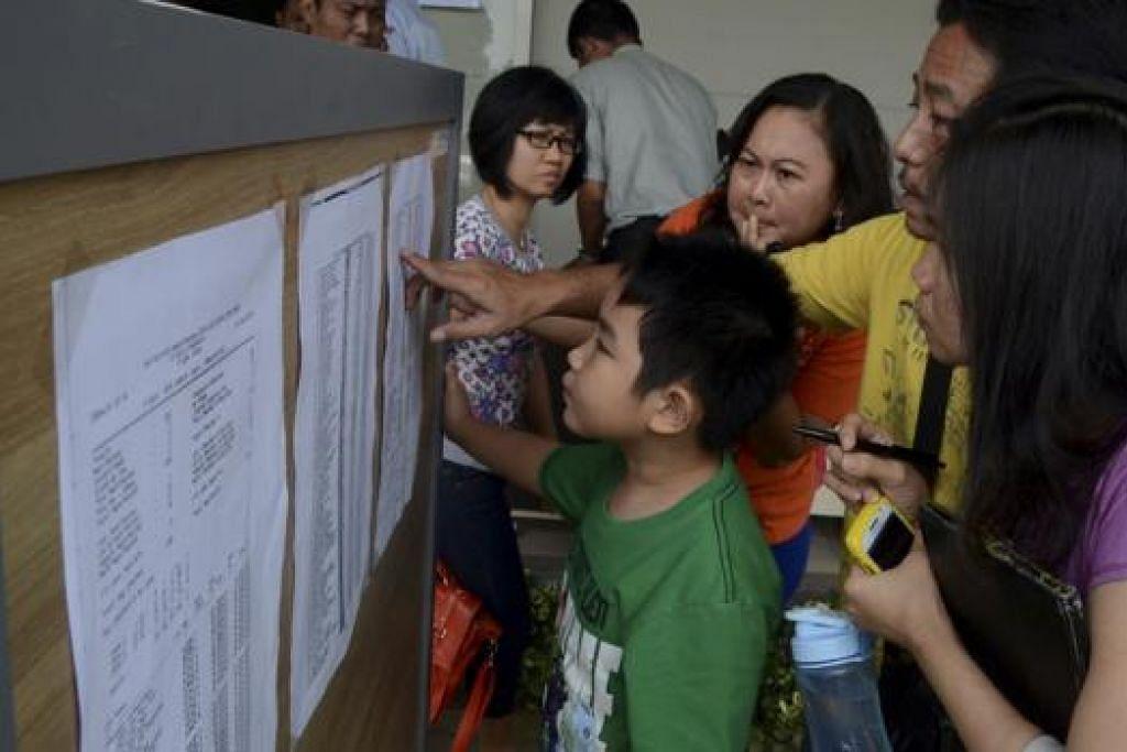 PERIKSA NAMA PENUMPANG: Anggota keluarga penumpang penerbangan AirAsia QZ8501 meneliti senarai penumpang di dalam pusat krisis di Lapangan Terbang Juanda di Surabaya semalam, sejurus menerima mengenai kehilangan pesawat tersebut awal pagi semalam. - Foto REUTERS