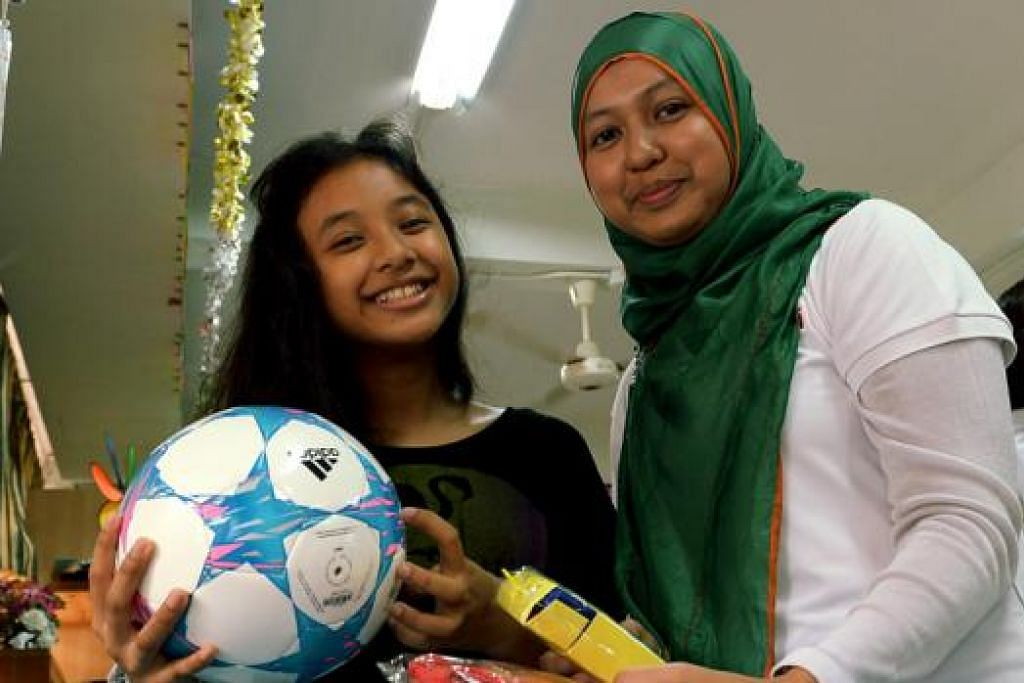 BERGEMBIRA BERSAMA: Nadia Adriana (kiri) gembira menerima sebiji bola yang telah diidamkannya serta alat tulis daripada seorang sukarelawan, Cik Nur 'Hanim Mohamed, dalam perayaan akhir tahun di Pusat Aktiviti Sunlove Senior semalam. - Foto TUKIMAN WARJI