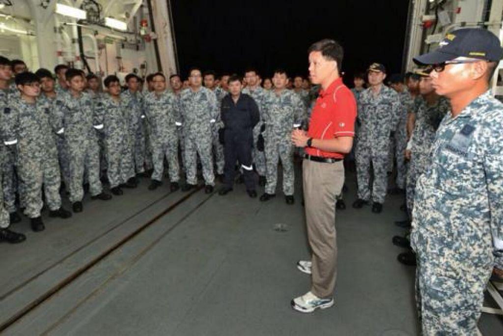 SIAP SEDIA: Encik Chan Chun Sing (berbaju merah) beramah-tamah dengan anggota tentera laut di atas kapal 'RSS Supreme' sebelum kapal itu dan sebuah lagi kapal tentera laut Singapura, 'RSS Valour', berlepas ke Indonesia untuk menyertai operasi mencari dan menyelamat pesawat AirAsia. - Foto MINDEF