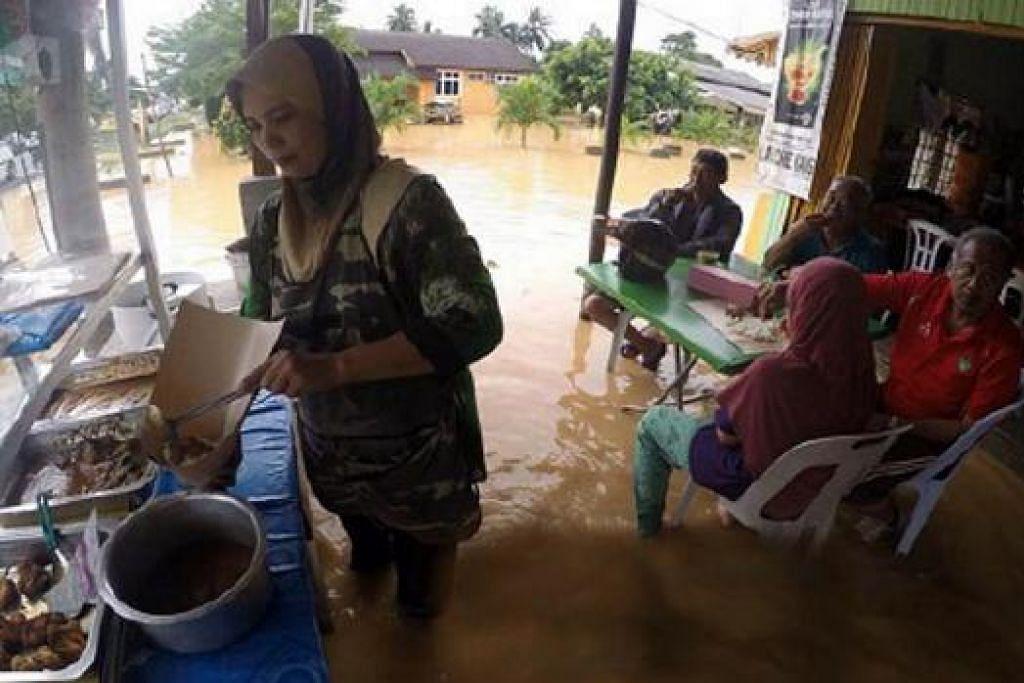 BERNIAGA DITERUSKAN: Walaupun banjir melanda, peniaga makanan tetap menyediakan jualannya di Kampung Kota, Kota Bharu. – Foto HARIAN METRO