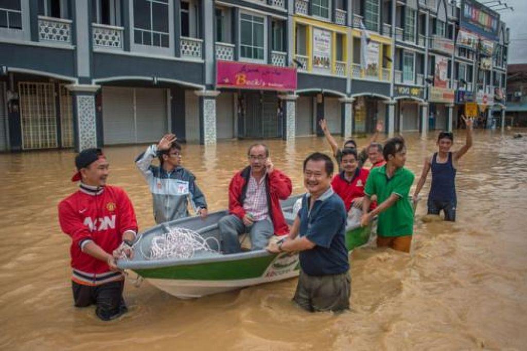 SAMPAN DI DARAT: Para penduduk di Kota Bharu menggunakan sampan untuk mengharungi banjir. – Foto AFP
