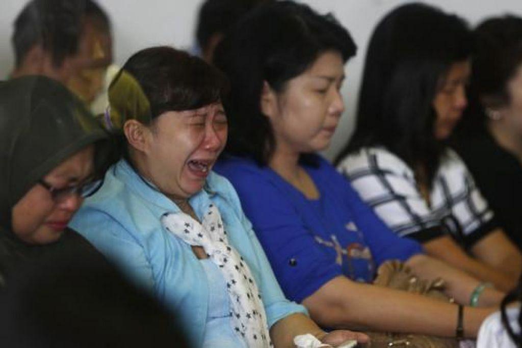 TIDAK PUTUS MENGHARAP: Ahli keluarga dan saudara-mara penumpang pesawat AirAsia penerbangan QZ8501 tidak dapat menahan sebak dan ada yang menangis semasa menunggu di Lapangan Terbang Antarabangsa Juanda, Surabaya, semalam. - Foto REUTERS