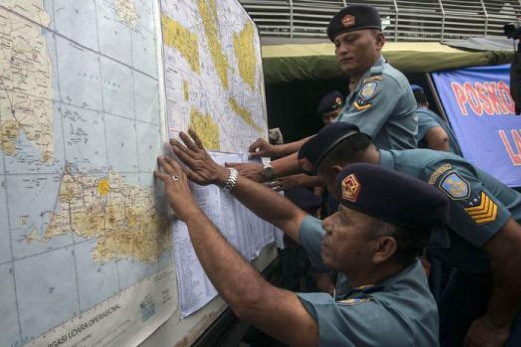 TEMPAT PENCARIAN: Pegawai Tentera Udara Indonesia menunjukkan peta kepada wartawan mengenai kawasan pencarian pesawat AirAsia yang hilang. - Foto AFP