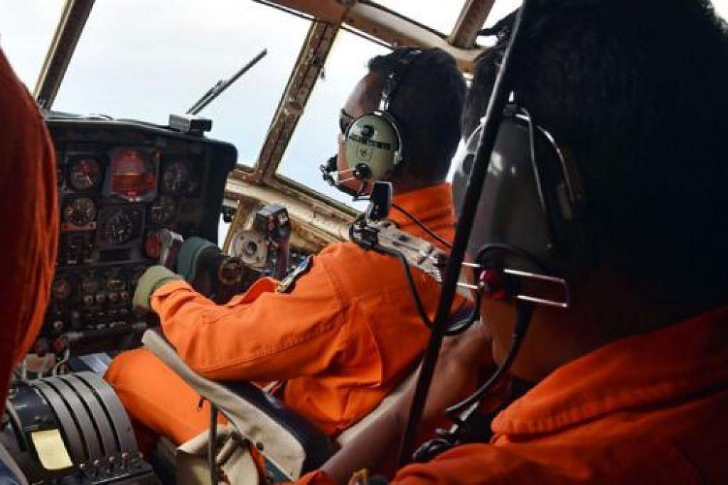 GIGIH MENCARI: Kakitangan tentera udara Indonesia menggunakan pesawat tentera C-130 Hercules untuk mencari pesawat AirAsia QZ8501 yang hilang di kawasan Laut Jawa. Pesawat Airbus AirAsia dengan 162 orang itu sedang dalam perjalanan dari Surabaya ke Singapura Ahad lalu apabila ia dilaporkan hilang. - Foto AFP