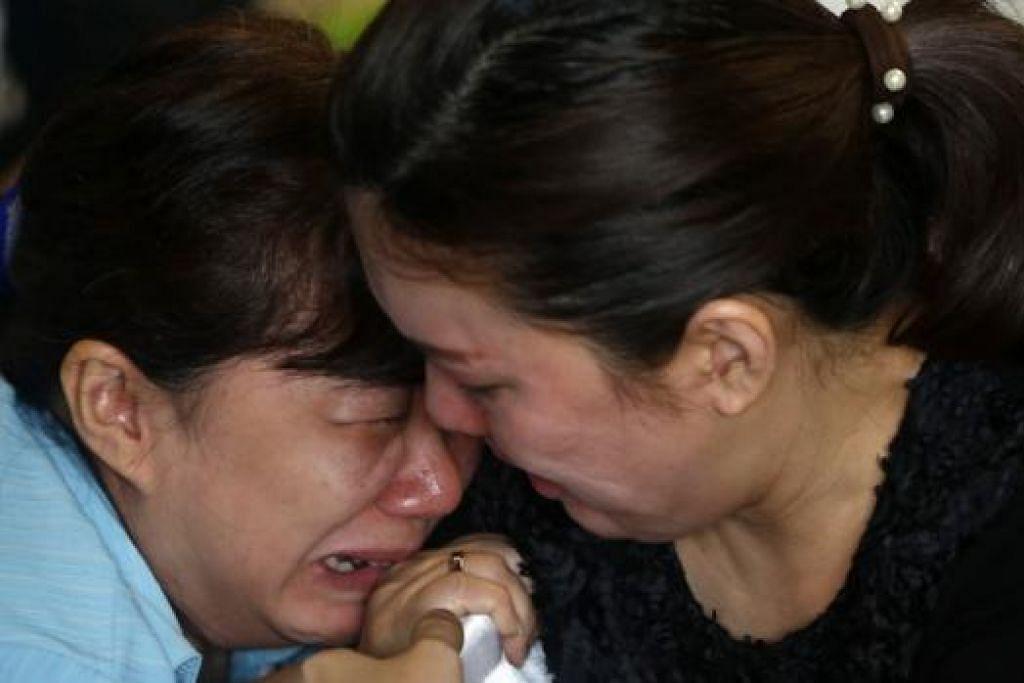 TERLALU SEDIH: Anggota keluarga penumpang pesawat AirAsia yang hilang sedang menangis di kawasan menunggu di Lapangan Terbang Antarabangsa Juanda sambil terus menanti perkembangan terkini tentang nasib penumpang. - Foto REUTERS