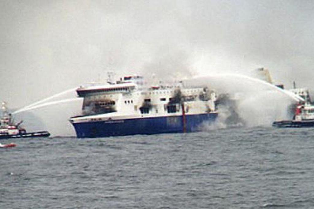 NAHAS DI LAUT: Bot tunda pemadam kebakaran menyembur air ke atas feri 'Norman Atlantik' yang terbakar di selatan Laut Adriatic kelmarin. Penumpang yang terperangkap di atas feri itu merayu supaya diselamatkan oleh kapal-kapal berdekatan yang berdepan dengan keadaan ribut. - Foto REUTERS