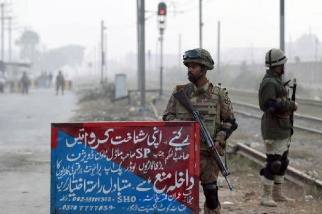 BERJAGA-JAGA: Tentera Pakistan berkawal di tempat pemeriksaan berhampiran Penjara Kot Lakhpat di pinggir Lahore Selasa lalu, berikutan keputusan pemerintah menggantung militan yang disabit kesalahan. Pakistan merancang melaksanakan hukuman mati ke atas sekitar 500 militan dalam beberapa minggu mendatang, selepas ia menarik balik larangan ke atas hukuman mati dalam kes keganasan. Ini berikutan pembunuhan beramai-ramai di sebuah sekolah elit tentera di Peshawar pada 16 Disember lalu yang dilakukan oleh Taleban yang mengakibatkan 149 orang mati termasuk 133 kanak-kanak. - Foto AFP