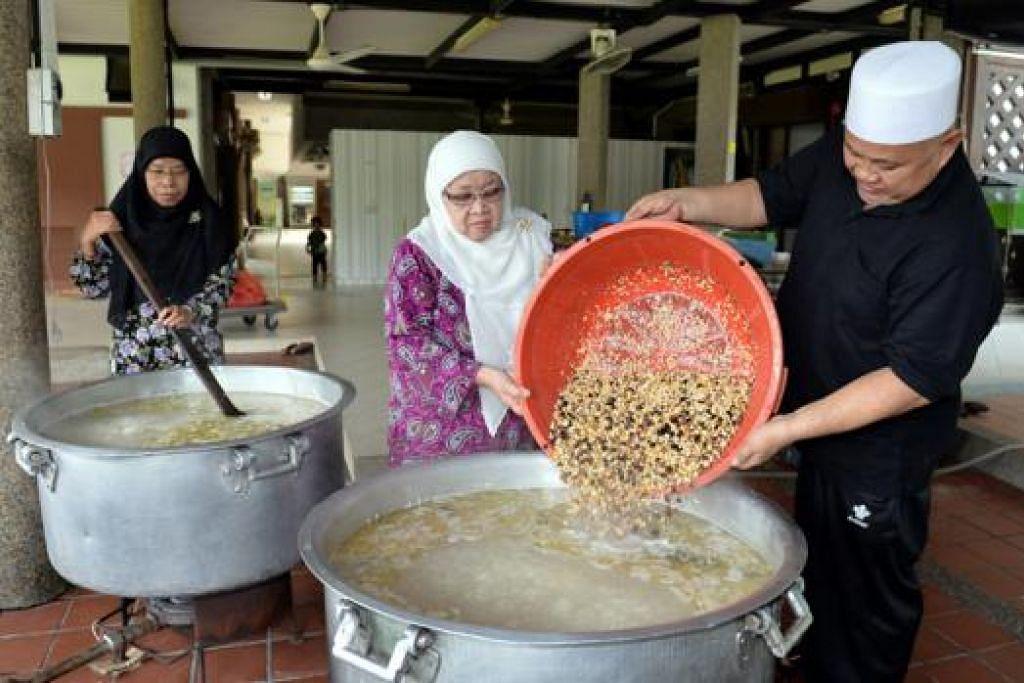 BERSAMA MASAK BUBUR: Haji Zainol Abidin Ahmad bersama Cik Beda Sahad (tengah), dibantu Cik Rafeah Haji Haron, memasak bubur Asyura di Masjid Darul Aman. - Foto: M.O. SALLEH