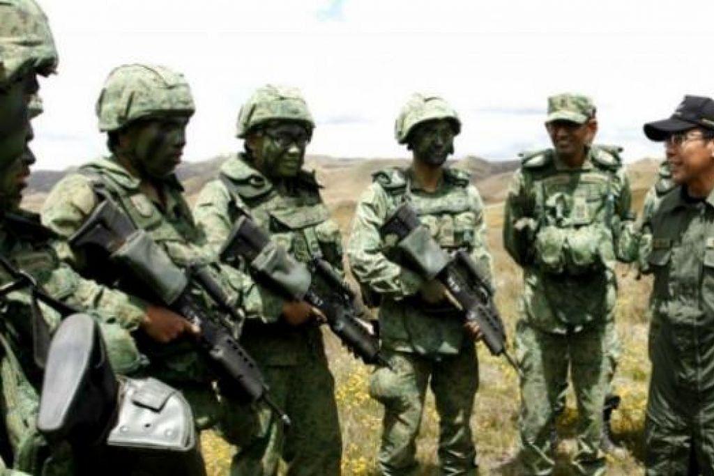 TINJAU KEADAAN: Dr Mohd Maliki (kanan) bersembang dengan askar SAF yang sedang menjalani latihan menembak artileri menggunakan peluru hidup di Kawasan Latihan Waiouru, New Zealand. Latihan itu menggariskan hubungan rapat antara tentera Singapura dan New Zealand. - Foto MINDEF