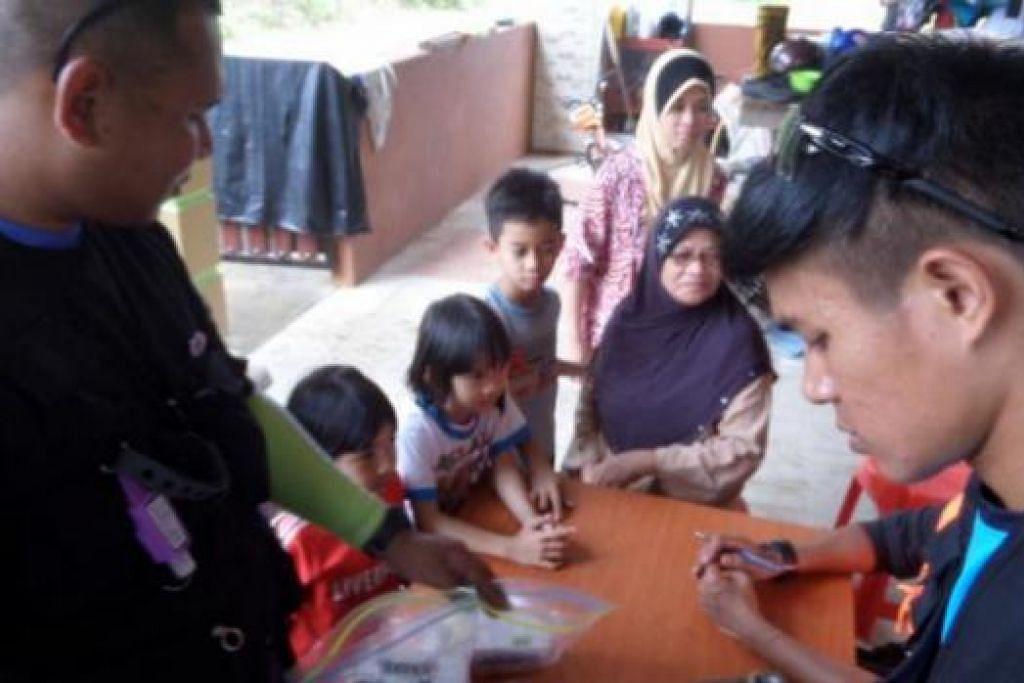 SEDIAKAN UBAT DI KLINIK SEMENTARA: Anggota sukarelawan dari Singapura mengagihkan ubat-ubatan kepada mangsa banjir di sebuah kilinik sementara yang mereka buka di Pekan, Pahang. - Foto-foto ihsan ALIAS ISMAIL