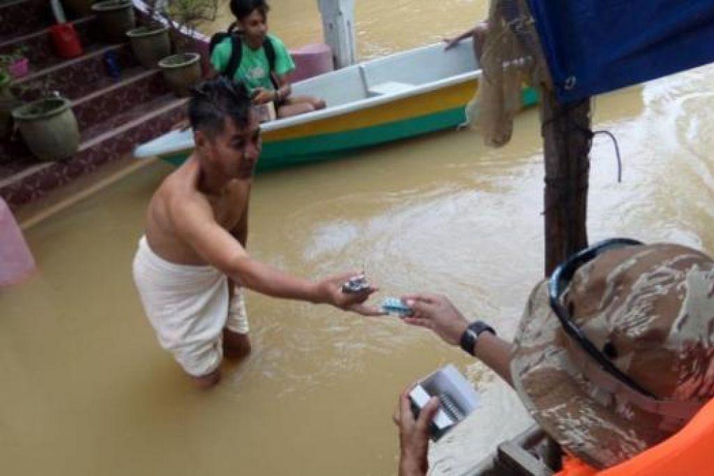 AGIH UBAT DARI RUMAH KE RUMAH: Seorang anggota sukarelawan dari Singapura memberi ubat-ubatan kepada seorang penduduk di hadapan rumahnya yang digenangi banjir. - Foto-foto ihsan ALIAS ISMAIL