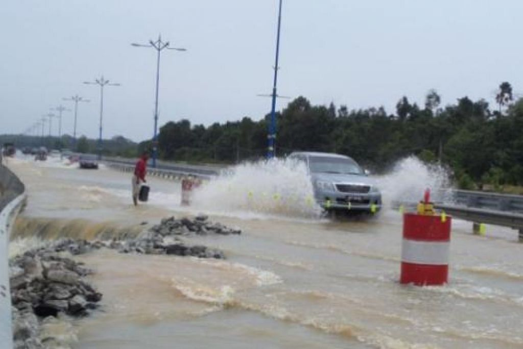 KEROSAKAN AKIBAT BENCANA BANJIR: Sebahagian jalan raya menuju ke Pekan, Pahang, ini rosak teruk akibat banjir yang melanda negeri di Pantai Timur Semenanjung Malaysia itu baru-baru ini. - Foto-foto ihsan ALIAS ISMAIL