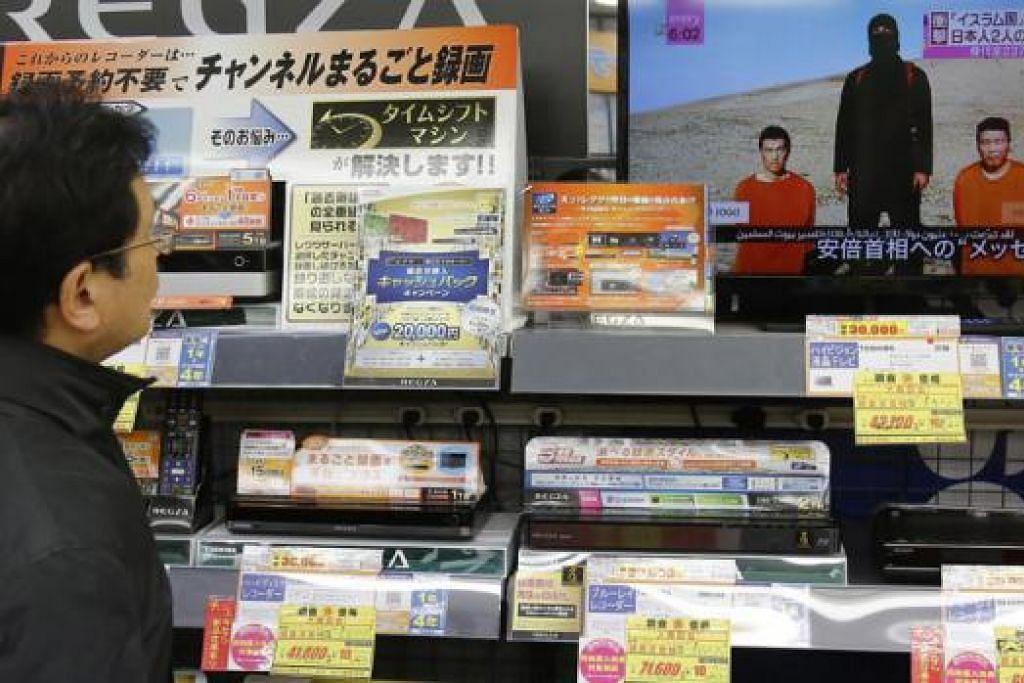 LIPUTAN MELUAS: Seorang lelaki menonton program berita mengenai video militan Negara Islam (IS) yang menculik dua warga Jepun semalam, di sebuah kedai elektronik di Tokyo. - Foto REUTERS