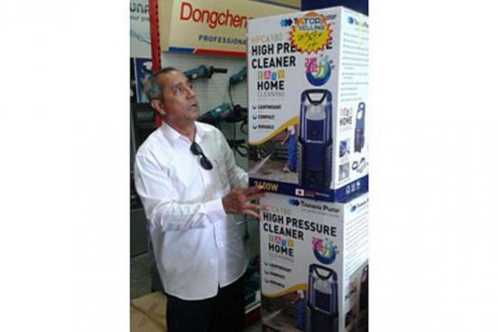 TERPANGGIL BERI SUMBANGAN: Encik Mohd Daud Mohd Bassar meneliti mesin penyembur air yang dibelinya di sebuah kedai di Sungai Buloh, Kuala Lumpur, sebelum menyerahkannya kepada sekumpulan sukarelawan untuk kerja pembersihan pasca banjir di Kelantan. - Foto SAINI SALLEH