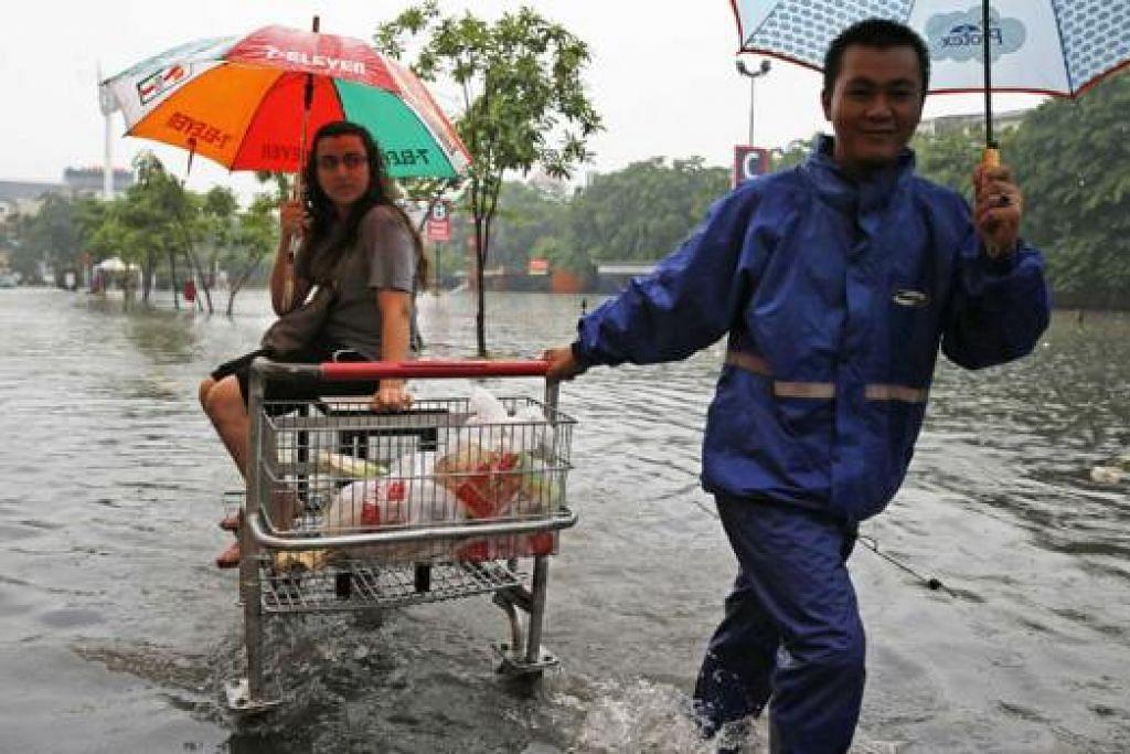 BANJIR TAPI TETAP BELANJA: Para pelanggan pasaraya Lotte Mart di kawasan perniagaan Kelapa Gading di Jakarta meredah air untuk ke tempat meletak kereta. - Foto REUTERS