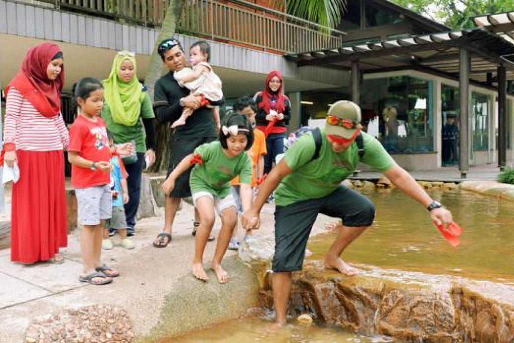 "PERBAIKI HUBUNGAN: Encik Mohd Rusdi Mohd Roshan, 26 tahun, memimpin anaknya, Nur Hannah Dayana, lapan tahun, di salah satu perhentian dalam permainan ""The Amazing Dads"" anjuran PPIS di Pantai Palawan, Sentosa. - Foto KHALID BABA"