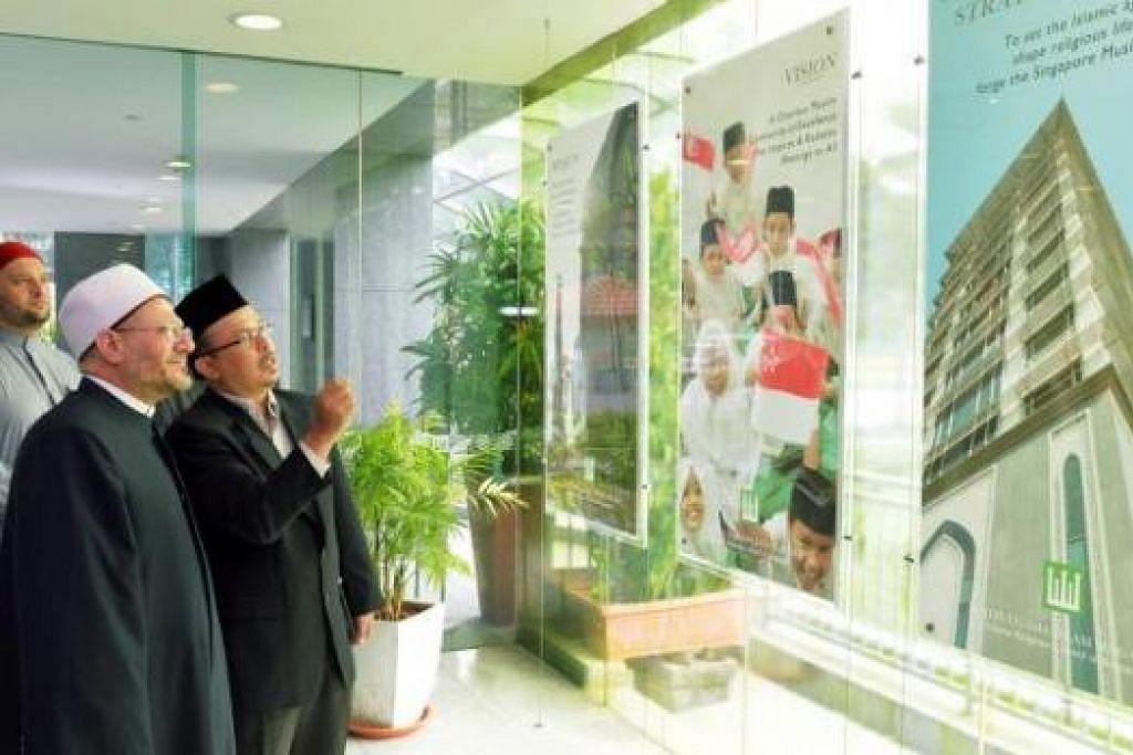 HAB ISLAM SINGAPURA: Ustaz Mohd Murat Mohd Aris menunjukkan pameran di bangunan Muis kepada Sheikh Dr Shawki dan Dr Ibrahim Negm, penasihat kanan Mufti Besar Mesir (belakang). – Foto KHALID BABA