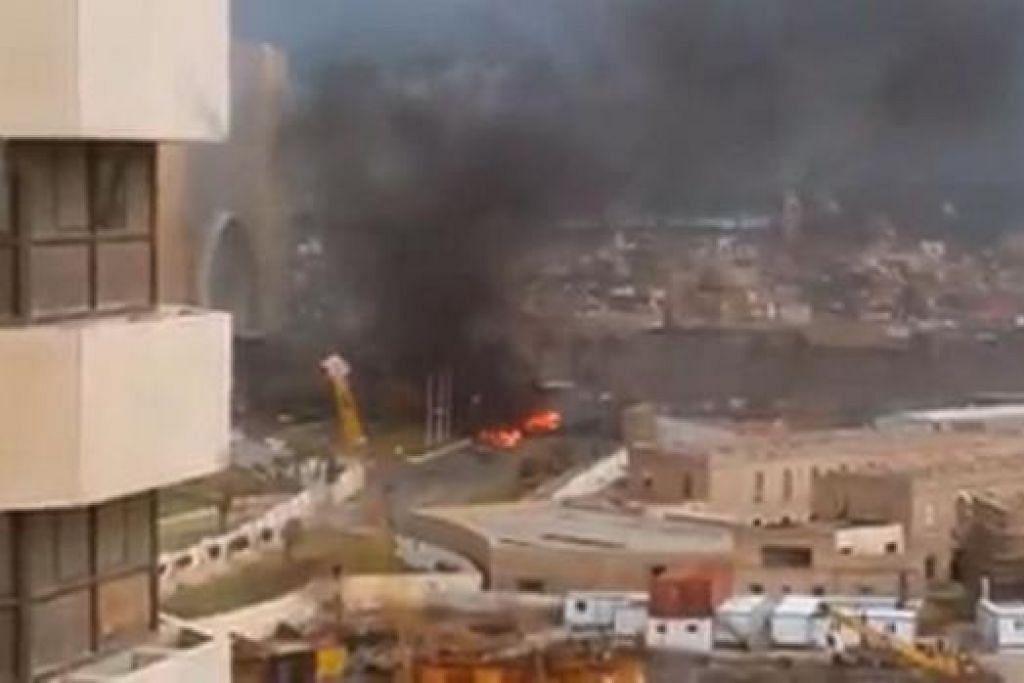 KESAN LETUPAN: Gambar yang diambil menunjukkan asap dan kebakaran di depan Hotel Corinthia di Tripoli selepas tiga lelaki bersenjata menyerbu masuk hotel mewah itu. - Foto AFP