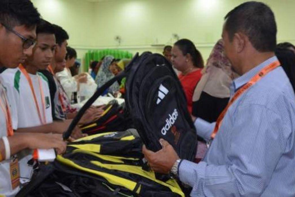 DAPAT BANTUAN: Para pelajar penerima habuan 'Program Kembali ke Sekolah' sibuk memilih beg yang diagihkan Persatuan Hira. - Foto-foto PERSATUAN HIRA