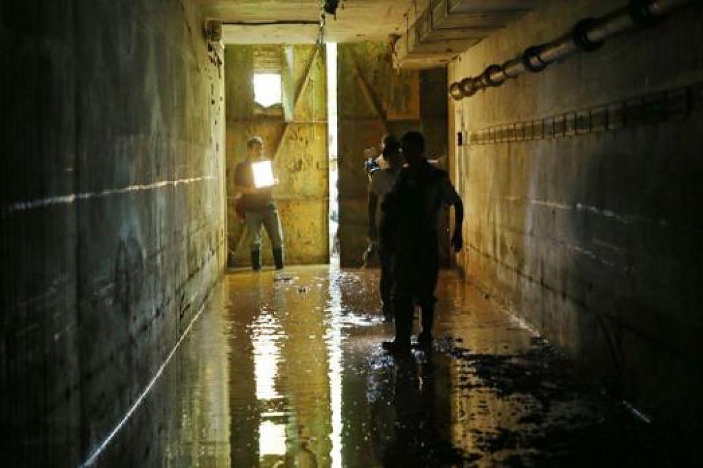 PENGALAMAN SENDIRI: Anggota media berjalan di dalam terowong berlumpur menuju ke kubu terakhir itu. Kubu itu akan dibuka kepada orang ramai untuk kali pertama bulan depan.