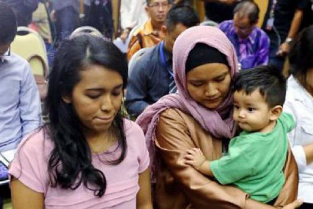 MASIH MENUNGGU JAWAPAN: Isteri pramagura Encik Mohd Hazrin Hasnan, Cik Intan Maizura, dan anaknya, Muhammad, di Putrajaya bagi menghadiri sidang akhbar DCA kelmarin. - Foto NSTP