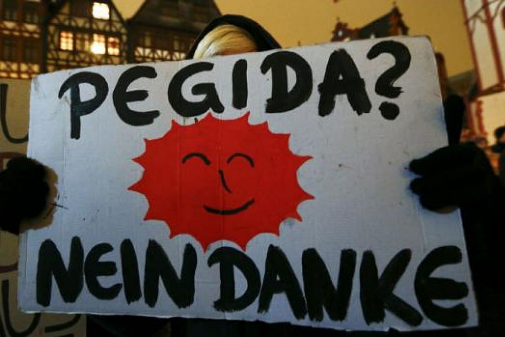 """TOLAK GERAKAN ANTIISLAM: Seorang penunjuk perasaan yang menentang pergerakan Pegida memegang sepanduk yang bermaksud """"Pegida? Tidak, Terima Kasih."""" di bandar Frankfurt, pada 26 Januari lalu. - Foto REUTERS"""