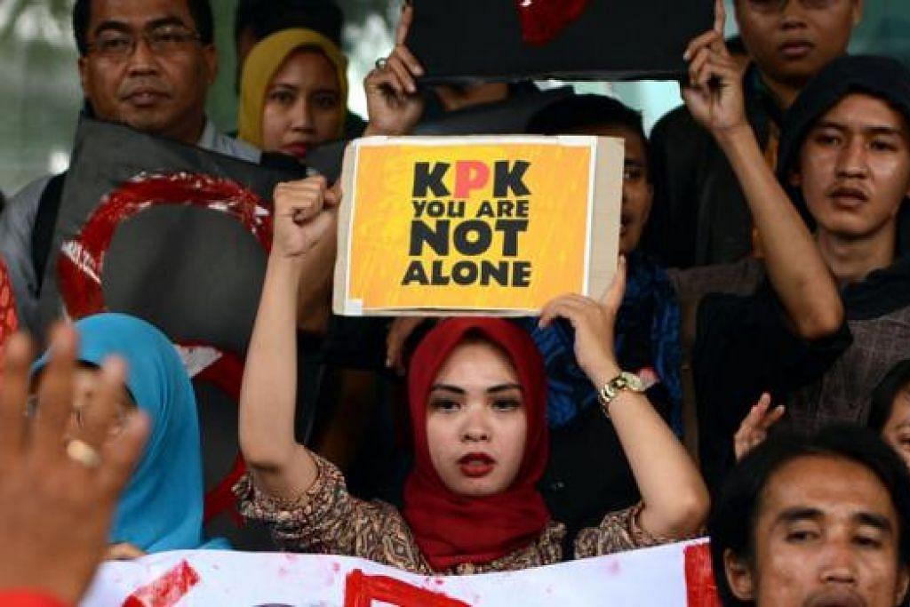 TUNJUK PERASAAN: Para penunjuk perasaan berkumpul di luar ibu pejabat Suruhanjaya Membasmi Rasuah (KPK), Jakarta, baru-baru ini untuk memberi sokongan kepada Timbalan Pengarah KPK, Encik Bambang Widjojanto. - Foto AFP