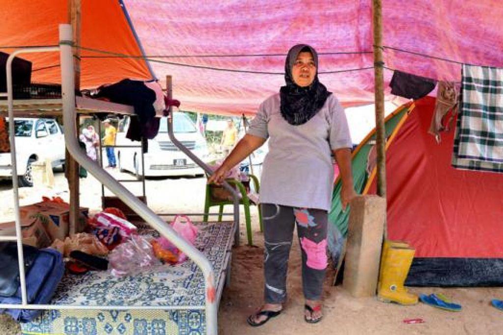 KHEMAH ISTANAKU: Cik Rozaini Ibrahim sekeluarga makan tidur di khemah yang didirikan oleh suaminya selepas rumah mereka dihanyutan banjir berserta arus deras dalam kejadian di Kampung Sat, Tanah Merah, Kelantan.