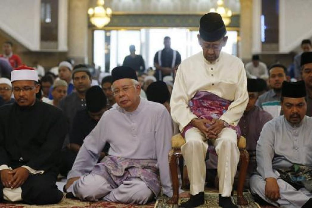 DOAKAN MANGSA: Tuanku Abdul Halim Mu'adzam Shah (duduk di kerusi) dan Perdana Menteri Najib Tun Razak (tiga dari kanan) di majlis tahlil bagi penumpang dan anak kapal pesawat MH370 di Masjid Negara, Kuala Lumpur. - Foto REUTERS