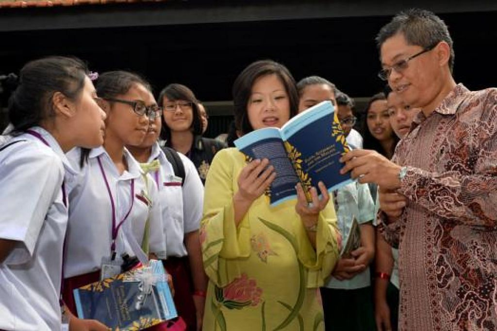 TINJAU KARYA: Cik Ann (dua dari kanan) melihat buku yang ditulis Encik Norshahril (kanan) sambil disaksikan para pelajar yang hadir di majlis pelancaran buku, laman dan aplikasi bertemakan warisan Melayu. FOTO: M.O. Salleh