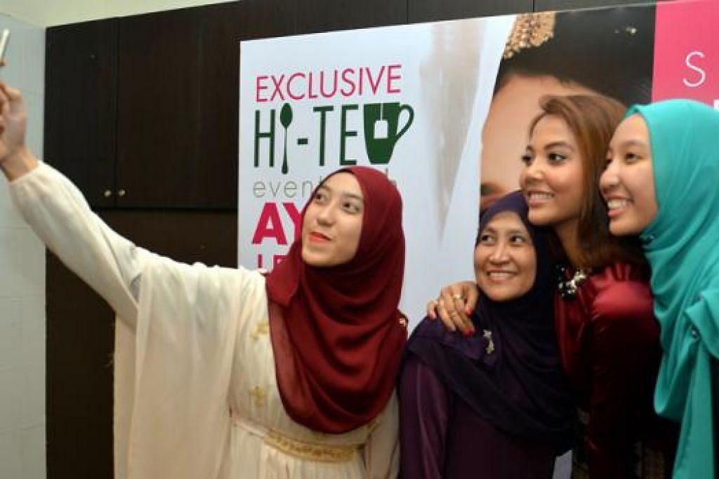 MARI SELFIE BERSAMA: Penyanyi Aisyah Aziz (dua dari kanan) meluangkan masa bergambar bersama beberapa peminatnya selepas menyanyikan lagu 'Mimpi' dan 'Tunggu Sekejap'.