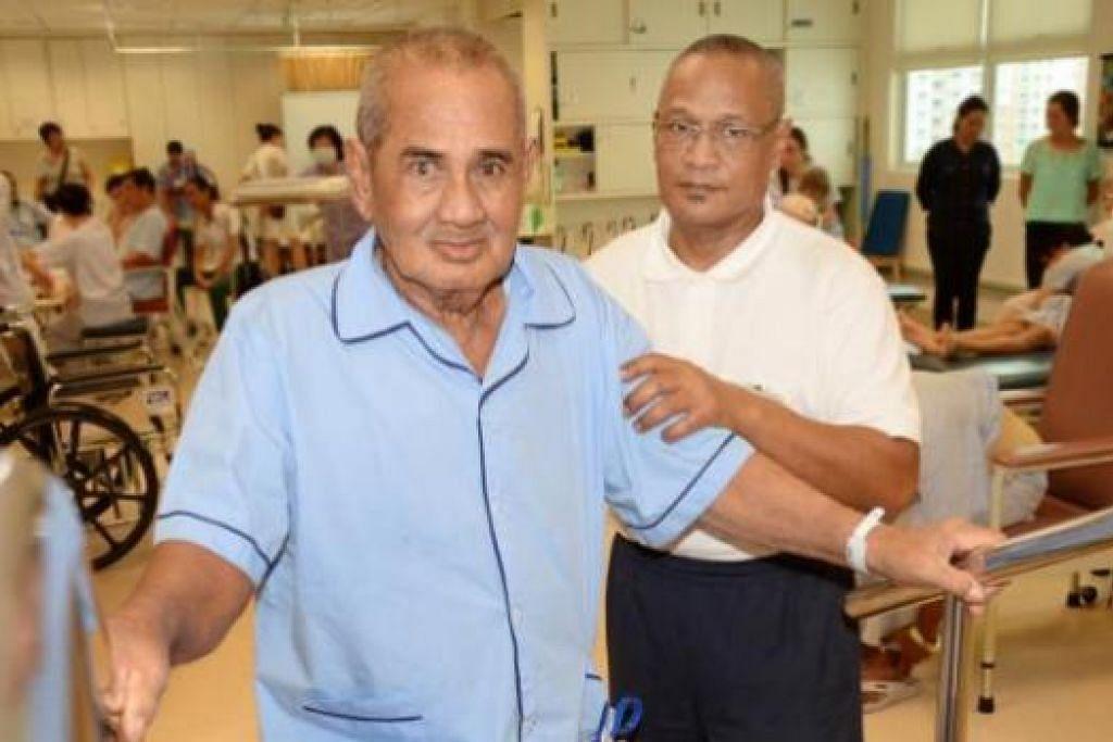 BANTU PEMULIHAN: Encik Rahmat (kanan) sedang membantu seorang pesakit, Encik Abdul Rahim Musa, menguatkan ototnya semasa menjalani terapi. - Foto JOHARI RAHMAT